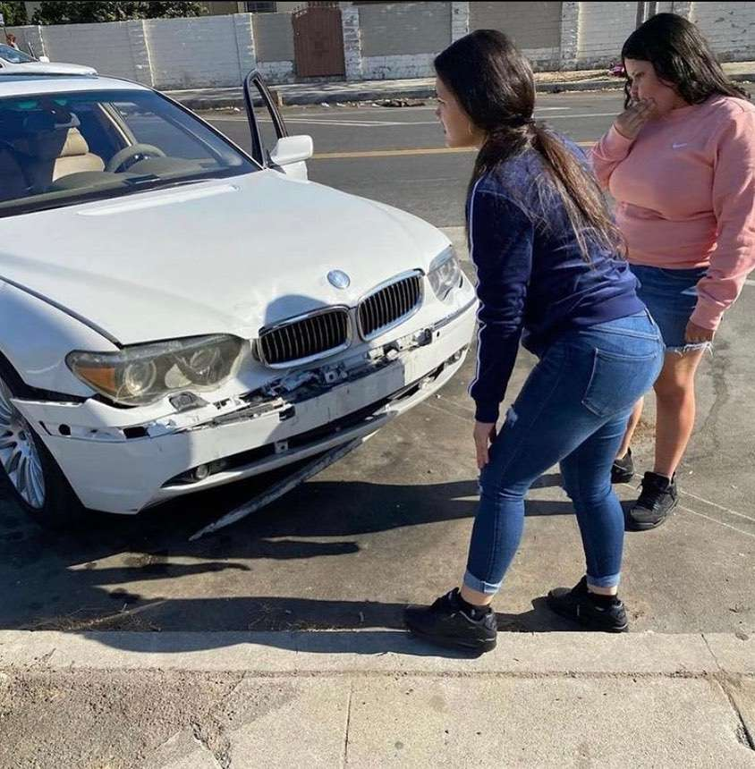 distracted BMW driver in Watts Los Angeles inspects damaage