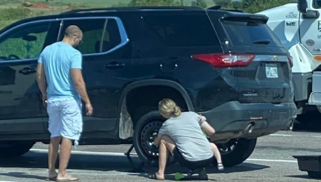 Mom with baby helps change a flat tire while husband watches